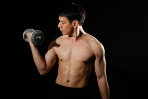 The man observes his arms while lifting the barbells.